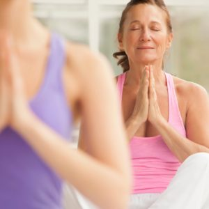 Seated woman in yoga class with peaceful, relaxed face