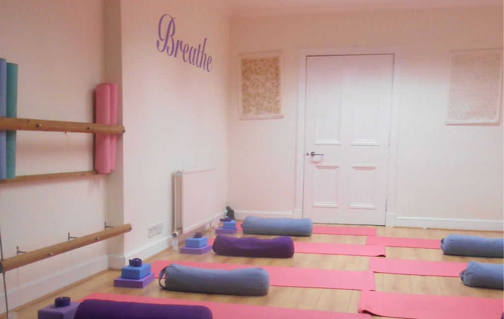 Yoga studio set out with yoga mats, with the word Breathe written on the wall